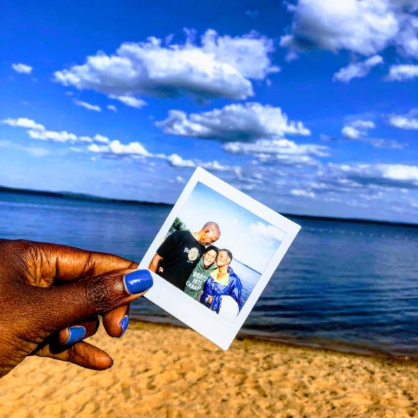Fingers holding a photo of grandparents and grandchild on vacation multigenerational travel